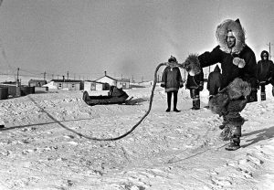 Prime Minister Pierre Trudeau tries cracking a dog sled whip while visiting Baker Lake in the Arctic, March 10, 1970. (CP PHOTO/ Peter Bregg)
